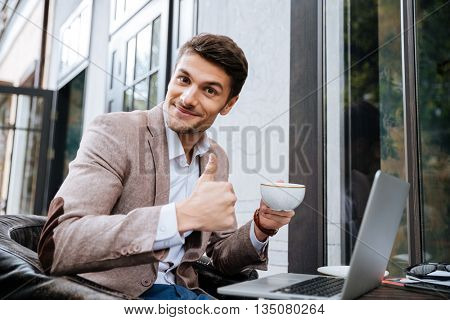 Smiling young handsome businessman holding cup of coffee and showing okay sign in cafe outdoors
