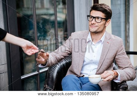 Smiling young man in glasses paying by credit card in outdoor cafe