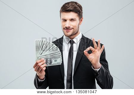 Confident young businessman holding money and showing ok sign over white background