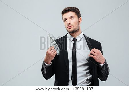 Tired young busnessman feeling hot and fanning with money over white background