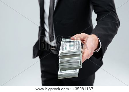 Closeup of businessman in suit and tie giving money to you over white background