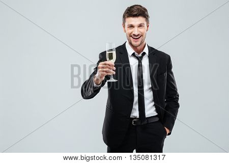 Smiling young businesman with glass of champagne standing and celebrating over white background