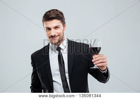 Smiling young businessman holding glass of red wine over white background