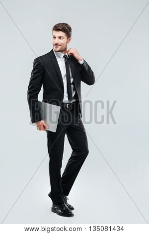 Full length of smiling young businesman with laptop over white background