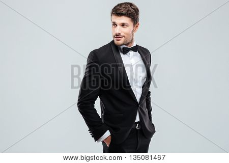 Attractive young man in tuxedo and bowtie standing over white background