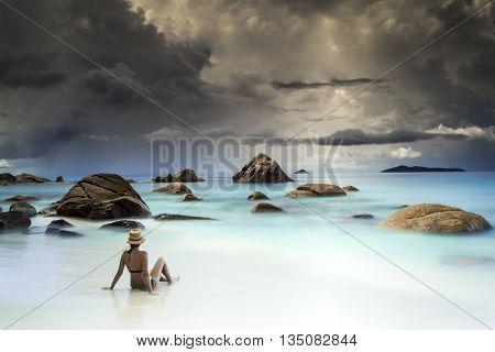 Woman resting at the beautiful Anze Lazio beach, Seychelles