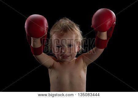 Boy athlete boxer or kickboxer gloves training. Black background.
