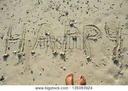 The inscription happy on sand and female feet, happy word written on sand of the beach