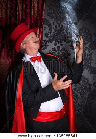 Funny magician making smoke out of his tuxedo sleeve