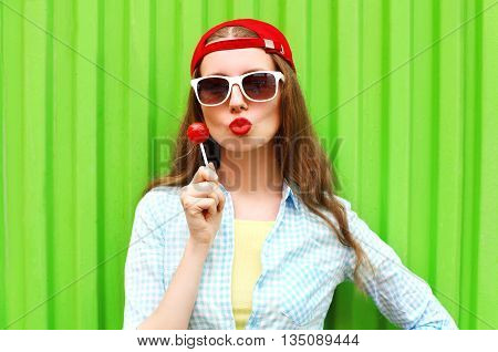 Fashion Portrait Pretty Cool Girl With Lollipop Over Green Backg