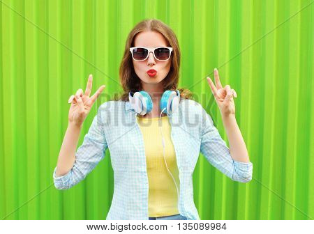 Pretty Cool Woman Listens To Music In Headphones Over Green Back