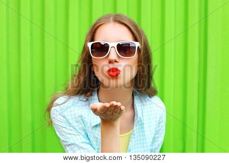 Woman In White Sunglasses Sends An Air Kiss Over Colorful Green