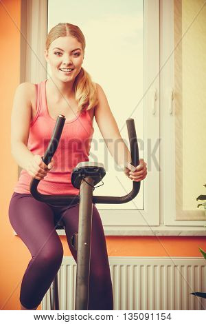 Active young woman working out on exercise bike stationary bicycle. Sporty girl training at home. Fitness and weight loss concept. Instagram filtered.