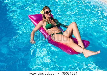 woman on air mattress in swimming pool water relaxing in summer