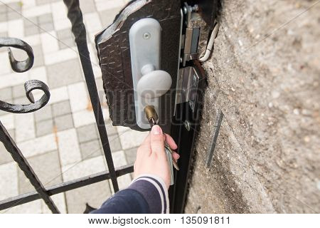 Hand use the key for unlocking and open the gate