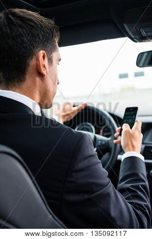 Man texting on his phone while driving by car