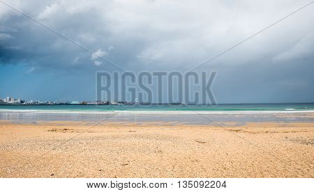 Tropical Sandy Beach With Storm Clouds And City In Background.