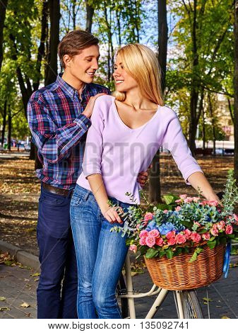 Young couple with bike in park on date. First romantic date.