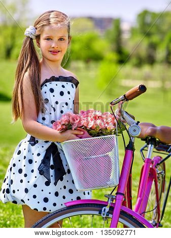 Bicycle girl child wearing white polka dots dress rides bicycle with pink flowers basket. Summer outdoor.