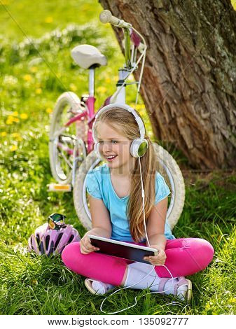 Bicycling girl. Girl rides bicycle. Girl wearing headset watching at tablet pc in cycling. listen music at pc computer. Cyclist looking at touch screen.