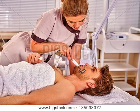 Man receiving electric facial peeling hydradermie at beauty salon.Man facial care.