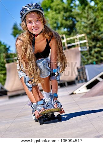 Teen wearing skateboard helmet skateboard on his skateboard and low crouch above her skateboard outdoor. Skateboard girl style.