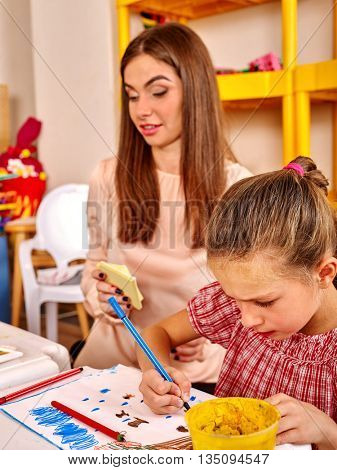 School girl with teacher woman painting on paper at table in primary painting school .
