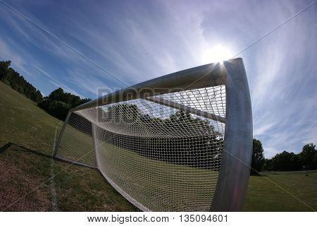 Fisheye photo of public soccer goal on field with green grass, and white lines.
