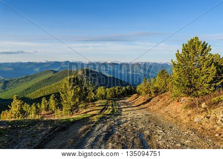 Scenic top view on the snow-capped mountain tops mountain slopes covered with forests the valley and the dirt road on a sunny summer day