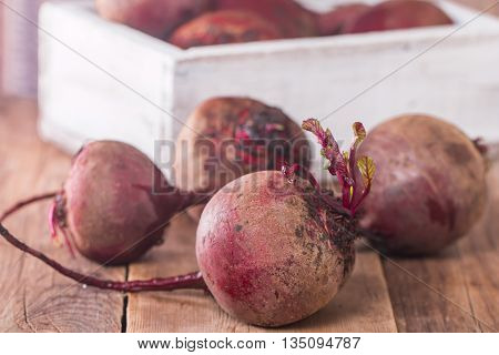 Fresh organic red beets in a wooden box on rustic background