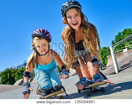 Two girl children in skateboard helmet skateboard on his skateboard outdoor. Low section.