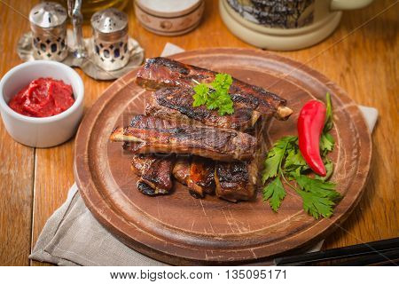 Close up view of barbecue pork ribs with tomato sauce on a old wooden table