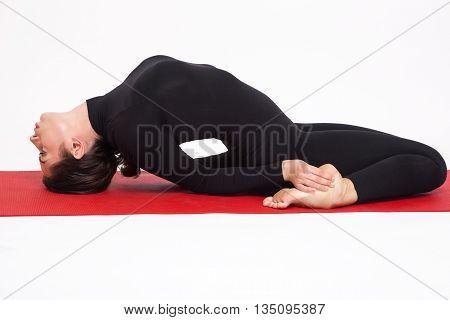 Beautiful athletic girl in black suit doing yoga. Matsiasana asana fish pose. Isolated on white background.