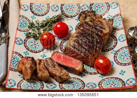 Sliced medium rare grilled Beef steak Ribeye with grilled cherry tomatoes on plate on wooden background, close up