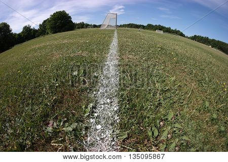 Fisheye photo of public soccer fields with green grass, white lines and goals.