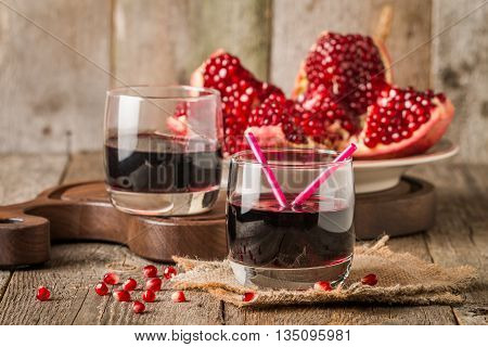Ripe pomegranates with juice on wooden table
