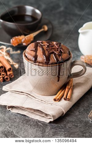 Chocolate souffle with  chocolate glaze in a cup on grey background