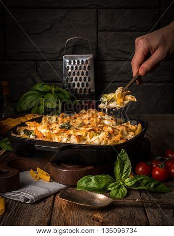 Baked pasta with broccoli, cauliflower, cheese and bechamel sauce in a frying pan with human hands in the frame  on wooden background