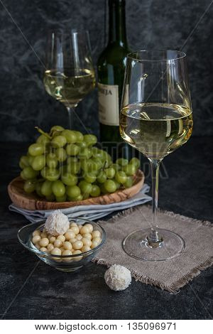 Bottle of white wine, two glasses and bunch of grapes on gray background