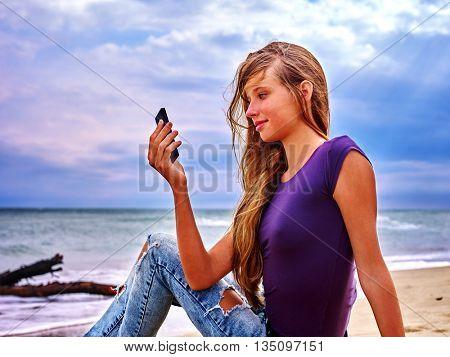 Teenager on sand near sea selfie by phone. Summer girl sea back on water.