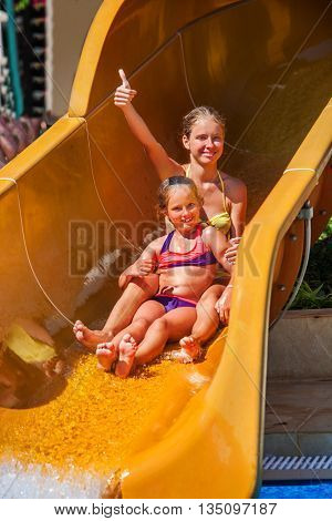 Two sister children at water park slide down water pool slide and give thumb up. Summer water slide holiday. Outdoor children water slide.