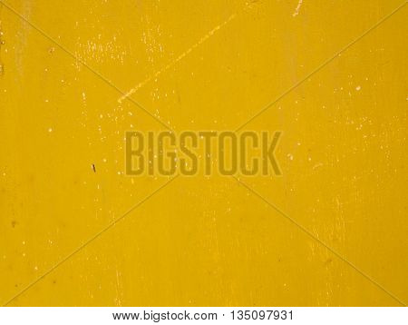 Rusty old metal surface painted in a dirty deep yellow color
