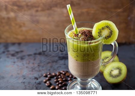 Double layer smoothie of chocolate and kiwi coffee ice-cream cocktail with straw on dark metal rusty table with brown background copy space at left