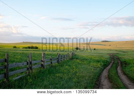 Rural road and an old fence in the early morning. The summer sunrise in the steppe of southern Siberia