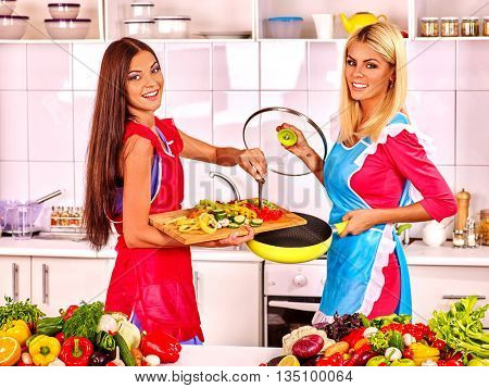 Two friends women preparing food at kitchen. Vegetarian preparing at kitchen.