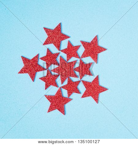 Red shining stars on a light blue background