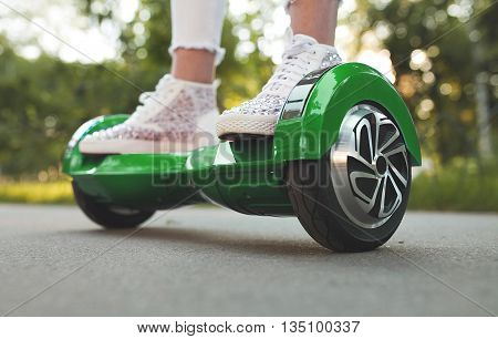 Woman feet  on the hover board. Modern  electric mini hover board gyroscooter outdoor. Mini Segway.