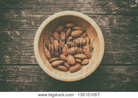 Dried almonds in wooden bowl. Retro filter.