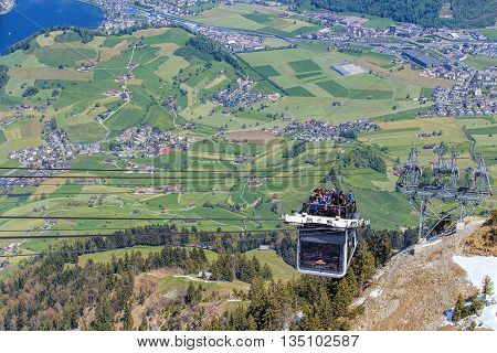 Mt. Stanserhorn, Switzerland - 7 May, 2016: people in a gondola of the Stanserhorn Cabrio cable car approaching the station on the top of the mountain. Stanserhorn Cabrio is the the world's first double deck open top cable car.