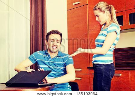 Man watching something on laptop, his wife is angry